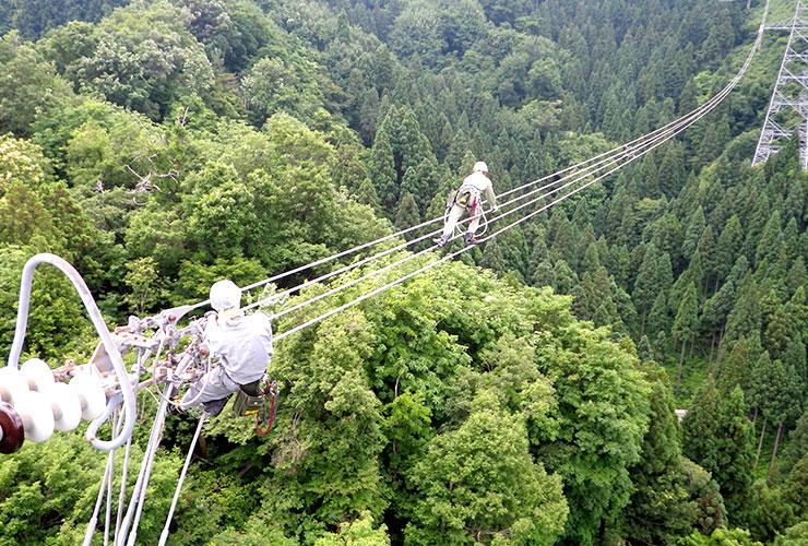 鉄塔から伸びる電線の上で作業する皆様