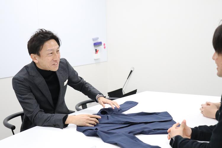 スーツ型作業服ステルスジャケットを社長に説明する野坂