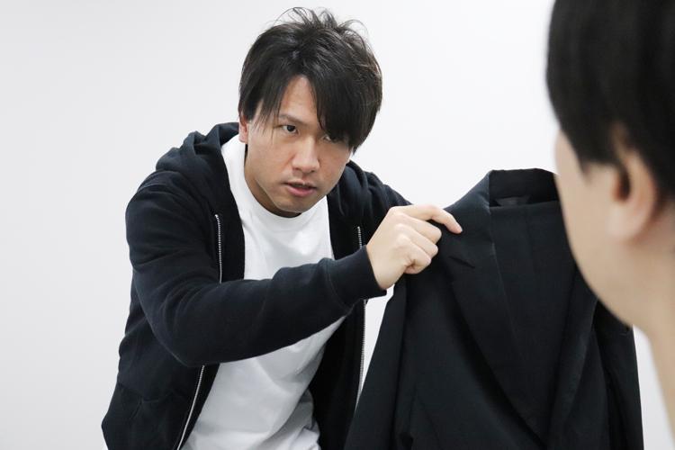 スーツ型作業服ステルスジャケットをカネさんに説明する野坂