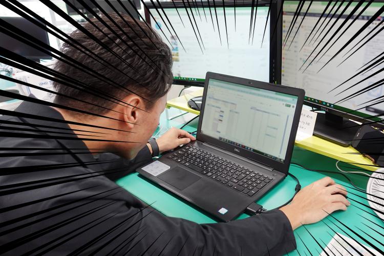 パソコン画面を見て驚くスタッフ野坂