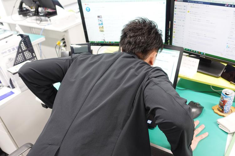 パソコン画面を見つめるスタッフ野坂